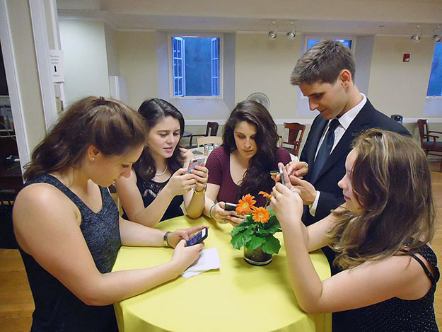 Young people texting on smartphones using thumbs