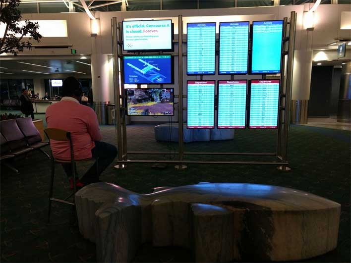Man Takes over Portland Airport Monitor to Play Video Game Apex Legends